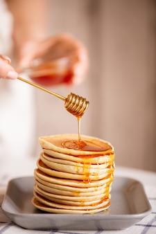 Hand der jungen hausfrau, die frischen honig vom schöpflöffel auf stapel des stapelns der appetitlichen hausgemachten pfannkuchen auf teller kocht, der zum frühstück gekocht wird