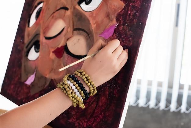 Hand der jungen künstlermalereifarbe auf segeltuch, kunstmalereiarbeit tuend