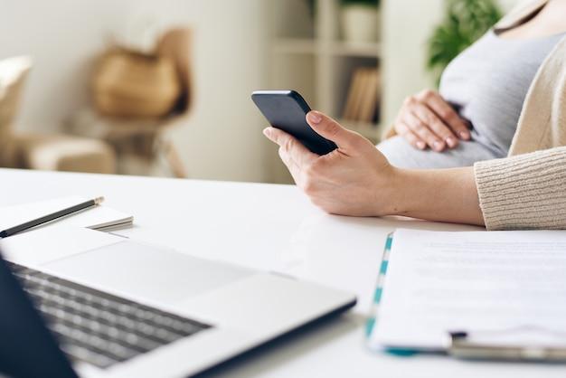 Hand der jungen schwangeren geschäftsfrau unter verwendung des smartphones beim sitzen am schreibtisch vor dem laptop in der büroumgebung und beim arbeiten