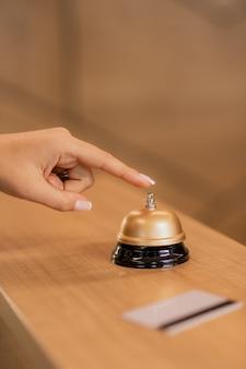 Hand der jungen zeitgenössischen geschäftsfrau, die anruftaste auf klingeln am empfangstresen im hotel drückt