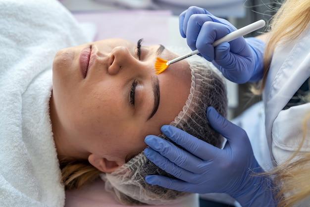 Hand der kosmetikerin, die feuchtigkeitscreme auf gesicht junge frau für behandlungstherapie und hautpflege aufträgt. konzept der sauberen und weichen körperhaut