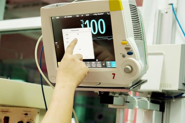 Hand der krankenschwestereinstellung der funktion an blutdruck-, lebenszeichen- und herzfrequenzmonitor im krankenhaus.