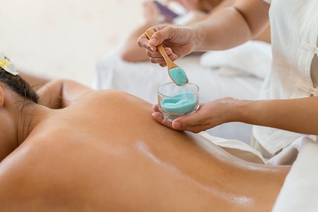 Hand der masseuse sprenkeln salz unten an der rückseite während junge asiatische frau im badekurort