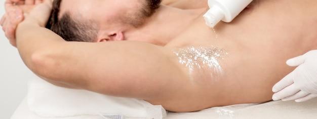 Hand der meisterdepilation, die talkumpuder auf die achselhöhle des jungen mannes vor dem enthaarungsverfahren gießt.