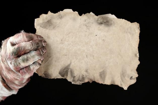 Hand der mumie, die altes papier lokalisiert auf schwarz hält