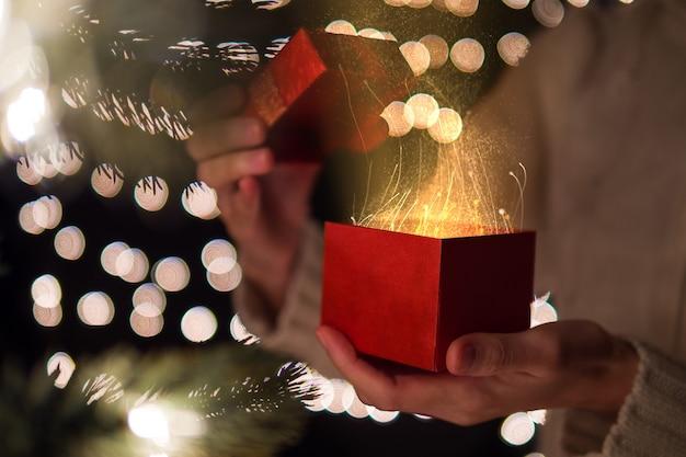 Hand der offenen roten weihnachtsgeschenkbox der frau mit goldenem strahl des magischen lichts auf bokeh beleuchtetem hintergrund