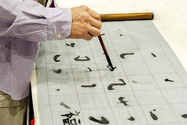 Hand der person chinesische bürste und chinesische zeichen der demonstration auf gewebe halten.