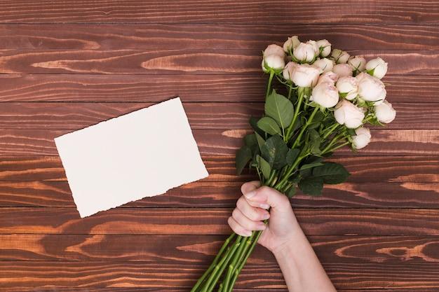 Hand der person, die bündel weiße rosen hält; leeres papier über schreibtisch aus holz