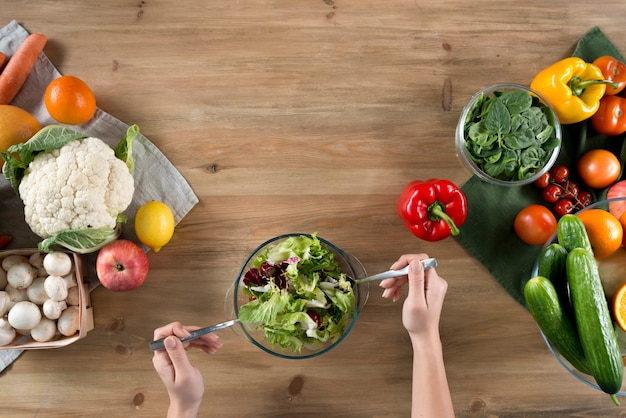 Hand der person, die frischen gesunden salat nahe vielzahl des gemüses und der früchte auf hölzerner küchenarbeitsplatte zubereitet