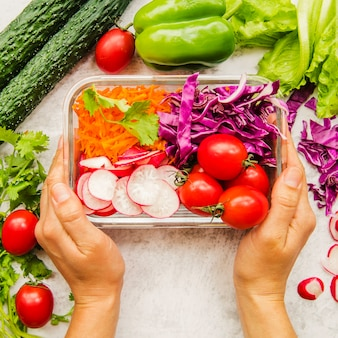 Hand der person, die frischgemüse und bestandteile für salat im behälter hält