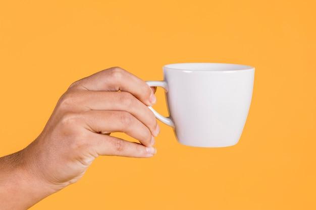 Hand der person, die kaffeetasse gegen farbigen hintergrund hält