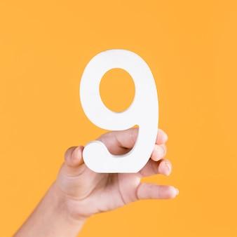 Hand der person, die nr. 9 auf gelbem hintergrund hält
