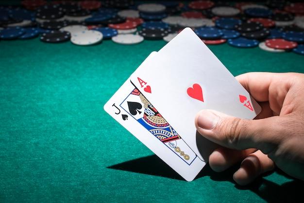 Hand der person, die pokerkarte im kasino hält