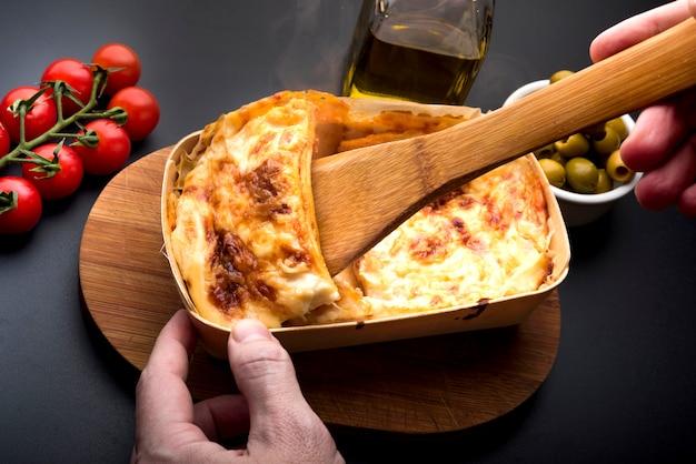Hand der person, die scheibe der lasagne mit hölzerner spachtel nimmt