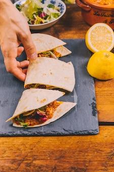 Hand der person, die scheibe eines mexikanischen rindfleisch tacos nimmt