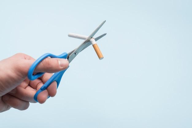 Hand der person, die zigarette mit schere über blauem hintergrund brokeret