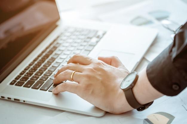 Hand der rührenden tastatur des büromannes für heruntergefahrenes computernotizbuch. er ist verheiratet.