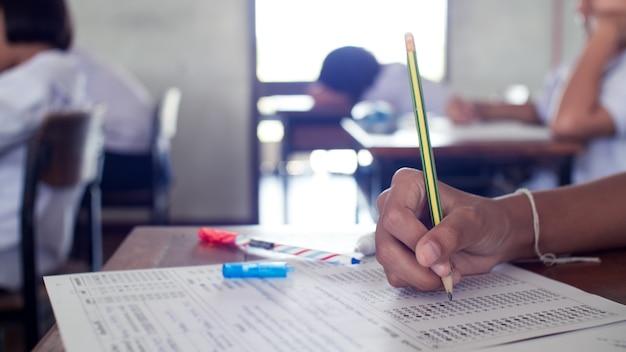 Hand der schüler, die mit stress im klassenzimmer schreiben und prüfung ablegen