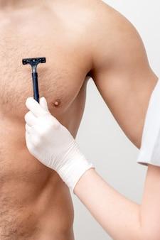 Hand der weiblichen kosmetikerin rasiert brust des mannes