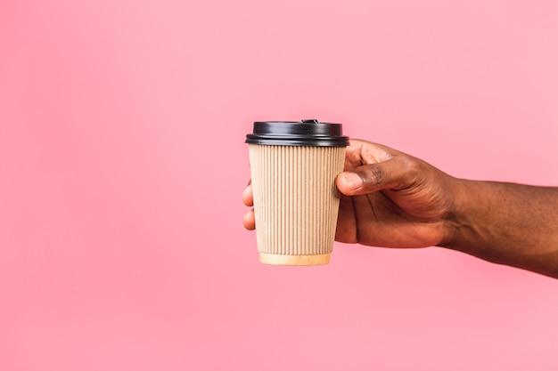 Hand des afroamerikanermanns, der papierkaffeetasse hält