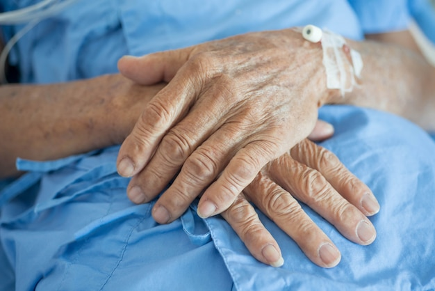 Hand des alten mannes, die in einem krankenhaus schläft