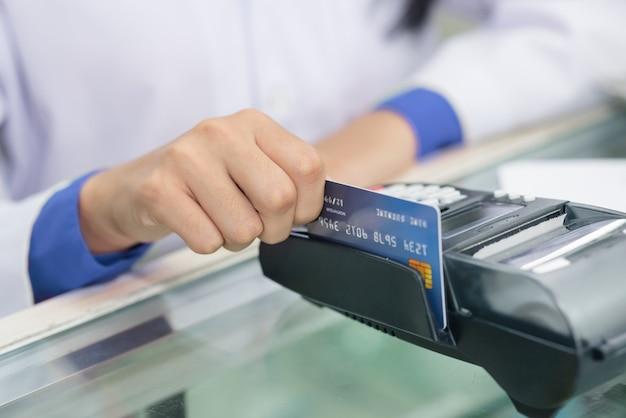 Hand des apothekers, des chemikers, der einkäufe tätigt, mit einer kreditkarte zahlt und ein terminal auf vielen medikamentenregal im apothekenhintergrund verwendet.