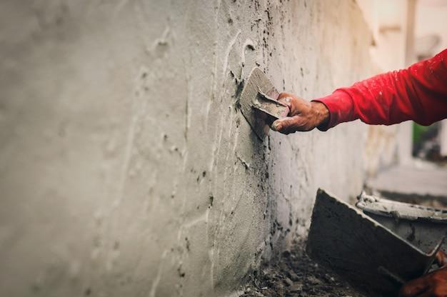 Hand des arbeiters, der zement an der wand für den hausbau auf der baustelle verputzt