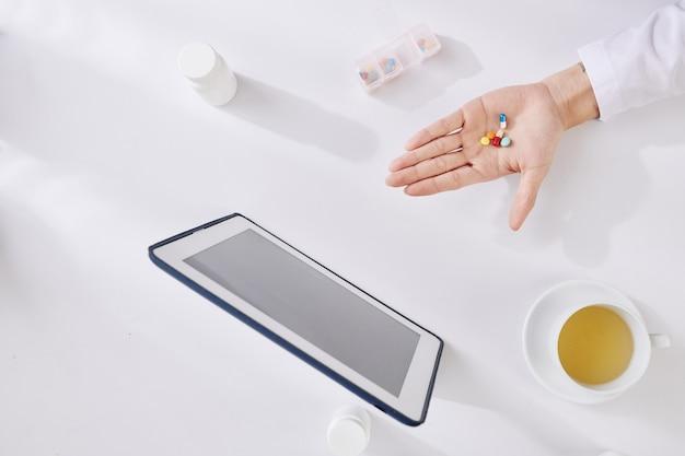 Hand des arztes mit pillen und tabletten