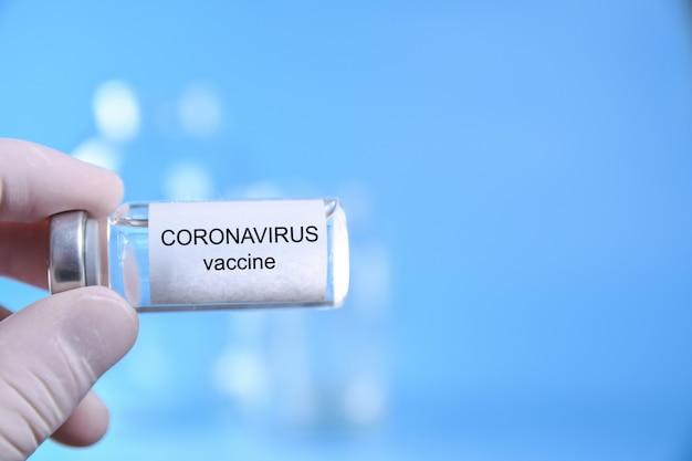 Hand des arztes oder der krankenschwester mit nitrilhandschuh, der coronavirus-impfstoffschuss für impfung, medizin und arzneimittelkonzept hält