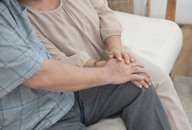 Hand des asiatischen älteren mannes und der frau halten zusammen, während sie zu hause auf der kutsche sitzen.