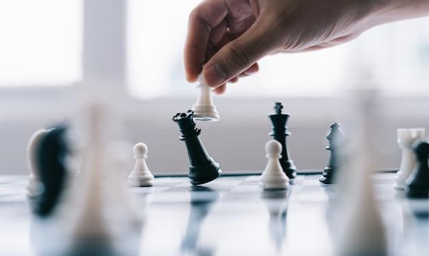 Hand des asiatischen geschäftsmannes, der schachfigur im wettbewerbserfolgsspiel bewegt