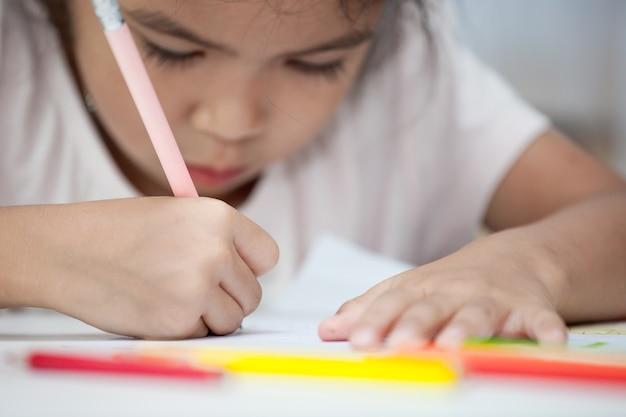 Hand des asiatischen kindermädchenabgehobenen betrages und -farbe mit zeichenstift