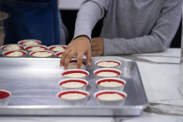 Hand des asien-kinderjungen einen kuchen machend