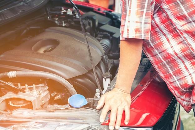 Hand des automechanikers mit einem schlüssel. autoreparaturmechaniker, der automotor im autoservice überprüft.