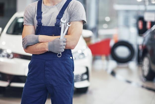 Hand des automechanikers mit schraubenschlüssel. autowerkstatt