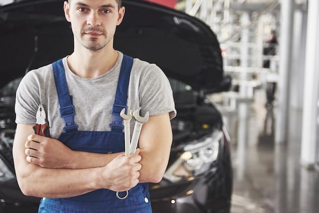 Hand des automechanikers mit schraubenschlüssel. autowerkstatt.