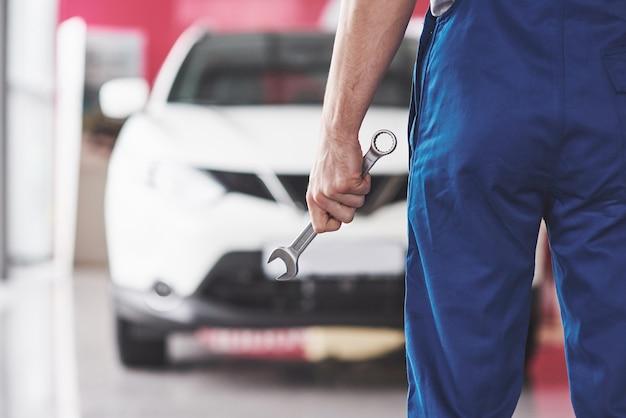 Hand des automechanikers mit schraubenschlüssel.