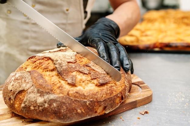 Hand des bäckers, der mit einem messer einen laib brot schneidet und mit schwarzen handschuhen schützt