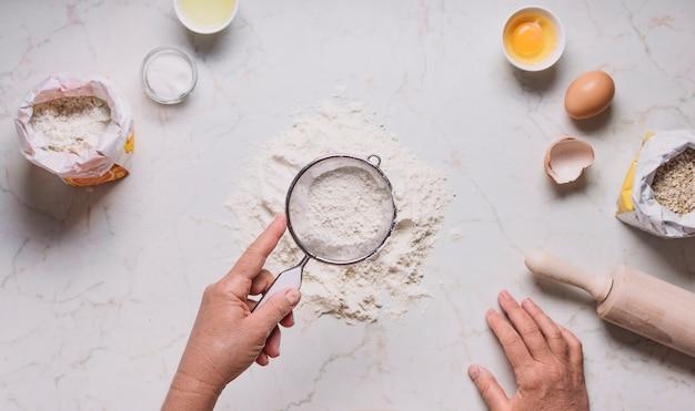 Hand des bäckers, die mehl durch sieb auf küchentheke sieben
