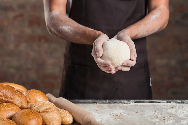 Hand des bäckers, die teig hält