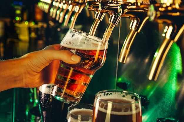 Hand des barkeepers, der ein großes lagerbier in den hahn gießt. helles und modernes neonlicht, männerhände. gießen von bier für den kunden. seitenansicht des jungen barkeepers, der bier gießt, während er an der bartheke steht.