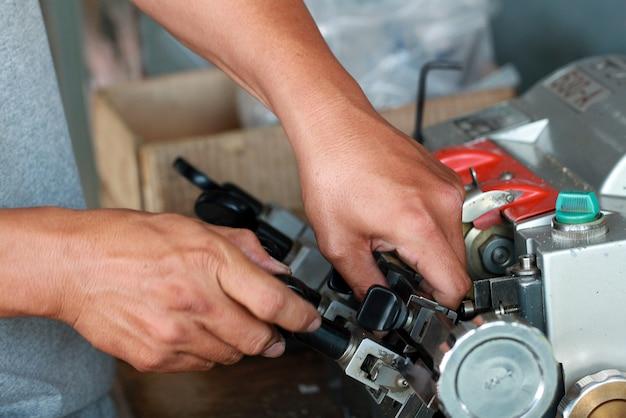 Hand des bauschlossers autoschlüssel mit schlüsselkopierer kopierend. nahe ansicht des schlüsselkopierers mit schlüssel. doppelte maschine machen neuen schlüssel