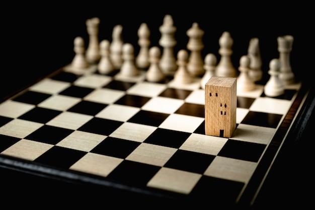 Hand des beweglichen schachs des geschäftsmannes zu den gebäude- und hausmodellen im schachspiel