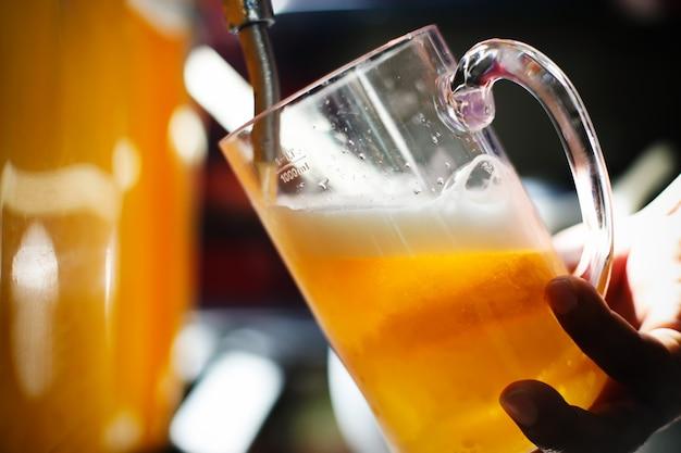Hand des bierhändlers am bierhahn, der ein fassbier gießt, das im restaurant oder in der kneipe serviert wird.