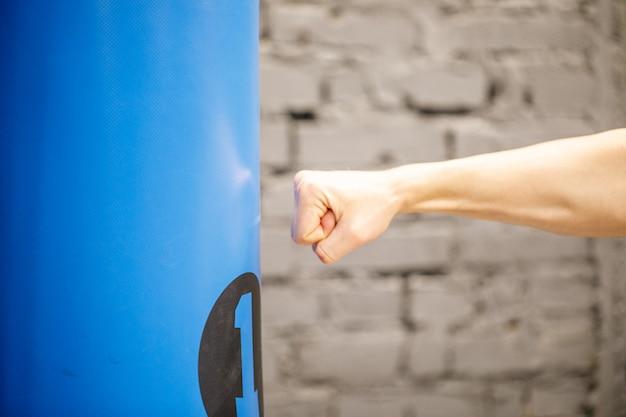 Hand des boxers und des blauen boxsacks im fitnessstudio.