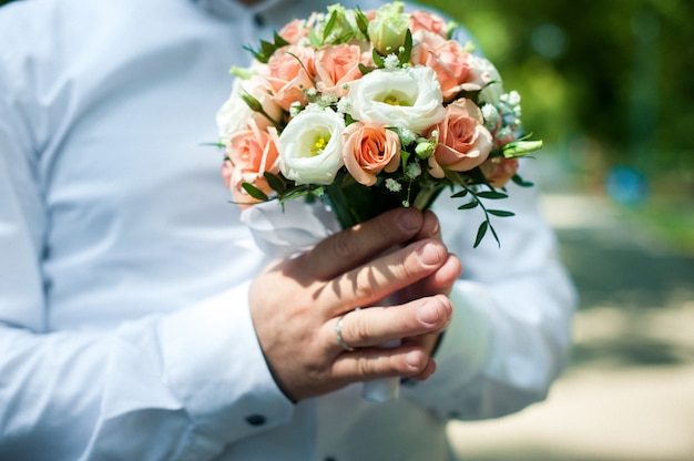 Hand des bräutigams, der den blumenstrauß der braut hält