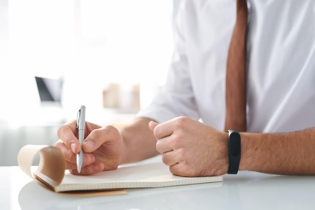 Hand des designers mit stift über leere seite des notizblocks beim brainstorming vor dem schreiben oder skizzieren