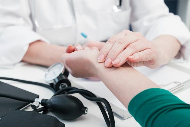Hand des doktors, die zu einem patienten neigt