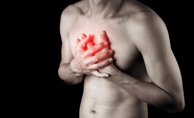 Hand des erwachsenen mannes, der brust mit schmerz berührt, verletzte schmerz auf schwarzen wandleuten, gesundheitskörperproblemkonzept