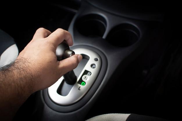 Hand des fahrers setzen einen schalthebel in position d (symbol) im auto-getriebewagen.